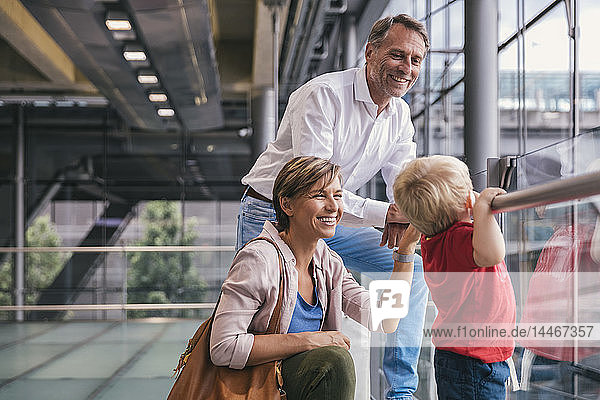 Happy family at the airport looking out of window