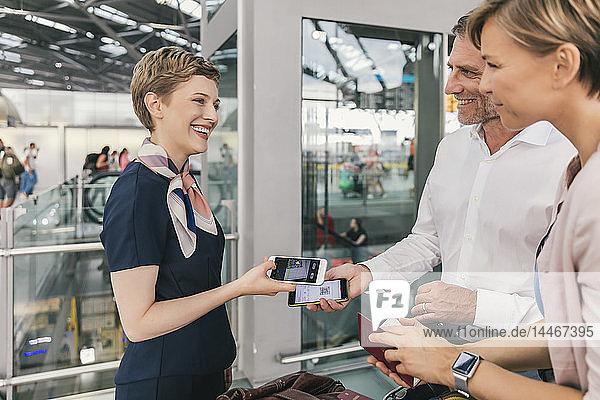 Mitarbeiter einer Fluggesellschaft scannt QR-Codes von Passagieren mit einem Smartphone am Flughafen