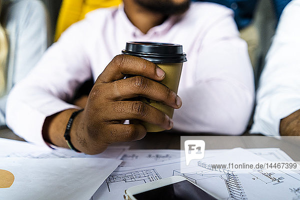 Close-up of businessman holding disposable coffee cup during a meeting in office