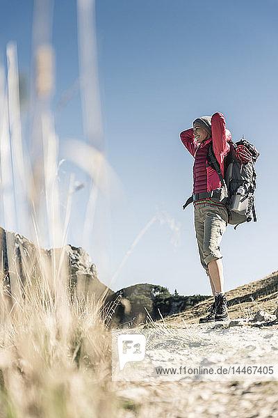 Österreich  Tirol  lächelnde Frau auf einer Wanderung in den Bergen  die die Aussicht genießt