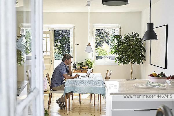 Ein reifer Mann sitzt in seinem Esszimmer und benutzt einen Laptop
