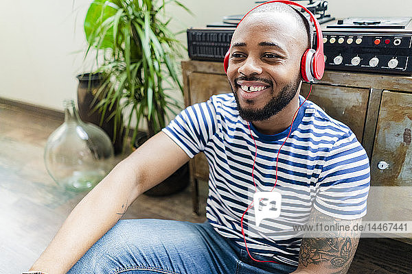 Happy young man with headphones sitting on floor in a loft