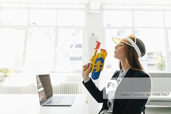 Junge Geschäftsfrau mit Wasserpistole in der Hand