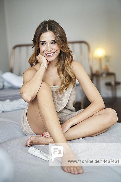 Porträt einer lächelnden jungen Frau auf dem Bett sitzend