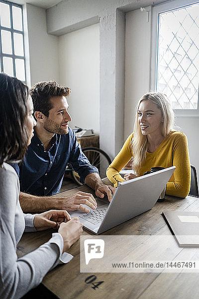 Geschäftsteam benutzt Laptop während einer Besprechung im Büro