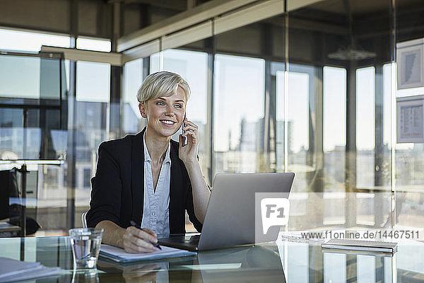 Lächelnde Geschäftsfrau arbeitet am Schreibtisch im Büro