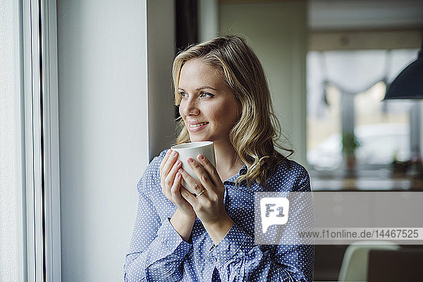 Smiling woman holding a cup of coffee at the window at home