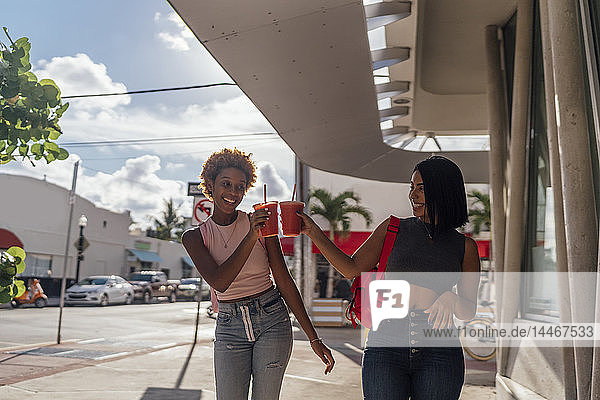 USA  Florida  Miami Beach  two happy female friends having a soft drink in the city
