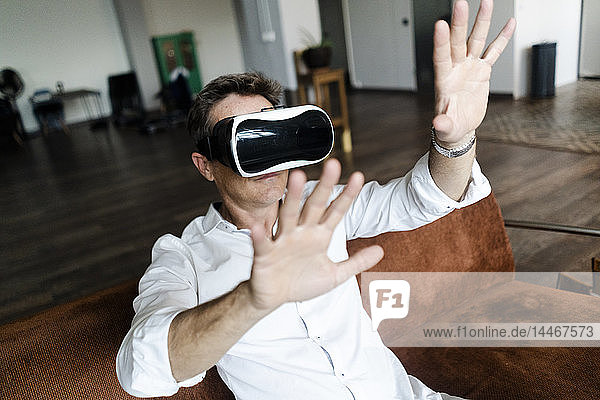 Mature man wearing VR glasses sitting on couch in a loft