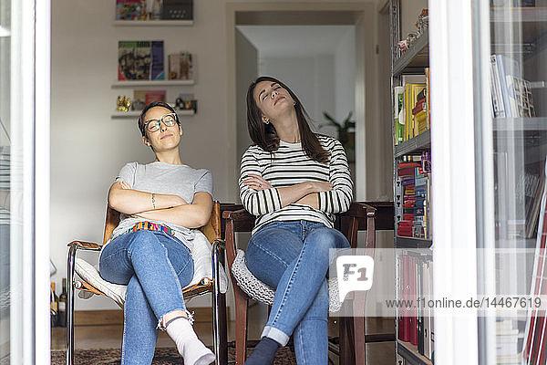 Zwei Freundinnen zu Hause  die bei offener Tür im Kitchem sitzen und die Sonne genießen