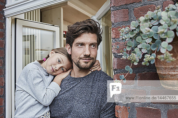 Portrait of father with daughter at house entrance of their home