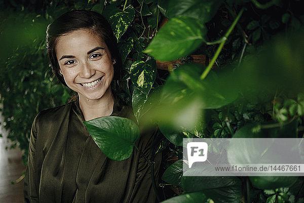 Porträt einer lächelnden jungen Frau an einer Wand mit Kletterpflanzen