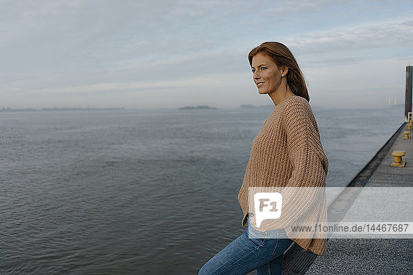 Germany  Hamburg  woman standing on pier at the Elbe shore