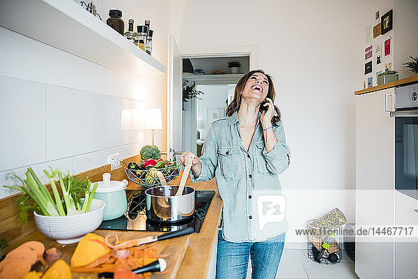 Laughing woman talking on the phone  while preparing pumpkin soup