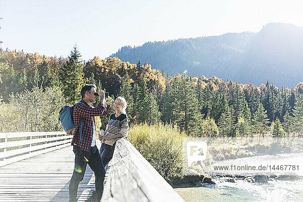 Österreich  Alpen  Ehepaar auf einer Wanderung mit Mann  der durch ein Fernglas schaut