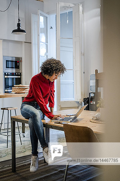 Young woman sitting on table using laptop