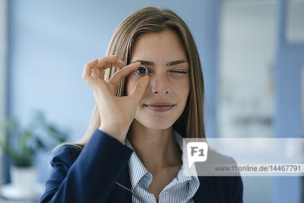 Junge Geschäftsfrau blickt durch einen laufenden Ring