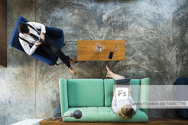 Draufsicht auf Geschäftskollegen  die am Laptop und Smartphone im Coworking Space arbeiten