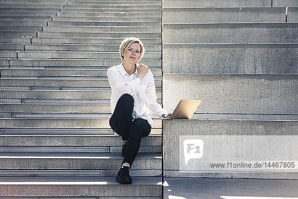 Junge Geschäftsfrau sitzt auf einer Treppe und benutzt einen Laptop