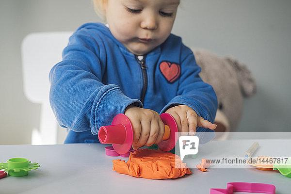 Mädchen spielt mit Knetmasse