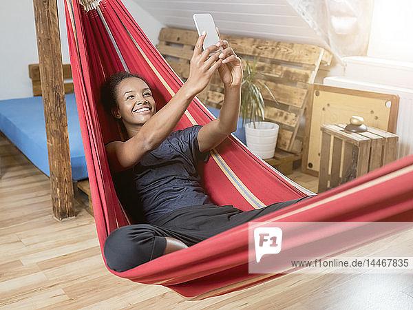 Lächelnde junge Frau in der Hängematte beim Selfie