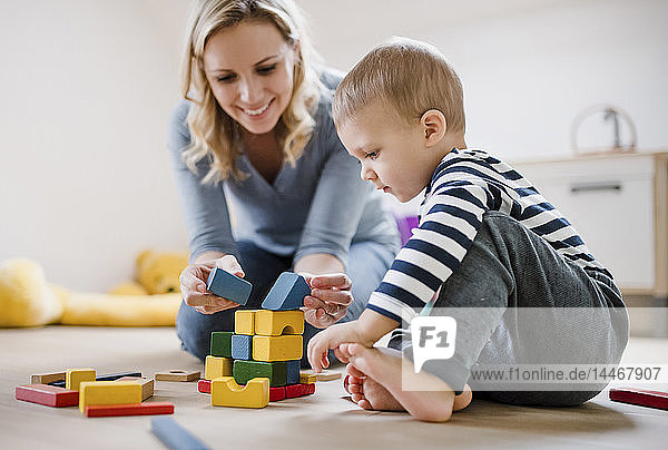Smiling mother and toddler son playing with building blocks at home