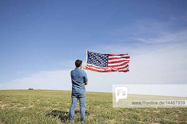 Man with American flag standing on field in remote landscape