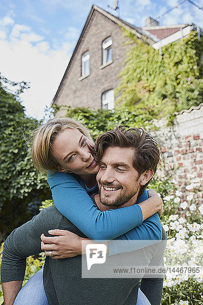Portrait of happy couple in garden of their home