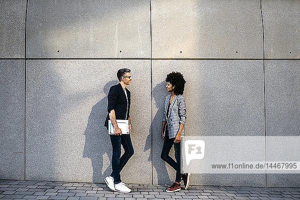 Zwei Kollegen unterhalten sich im Freien und lehnen sich an eine Wand