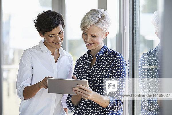 Zwei lächelnde Geschäftsfrauen betrachten Tablette am Fenster im Büro