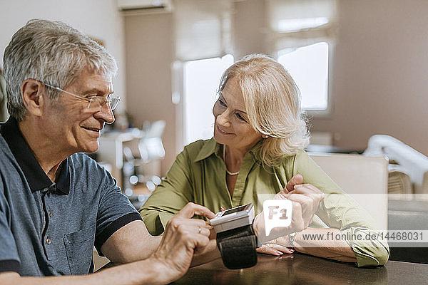 Lächelndes älteres Paar bei der Blutdruckmessung