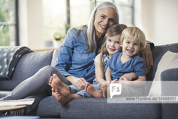 Grandmother sitting on couch with her grandchildren
