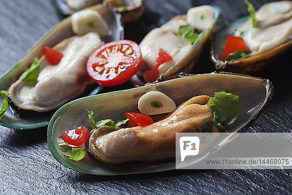 Grüne Muscheln mit Tomaten  Paprika und Knoblauch  auf schwarzer Schiefertafel