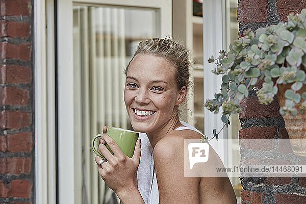 Portrait of smiling sporty young woman with cup of coffee at house entrance