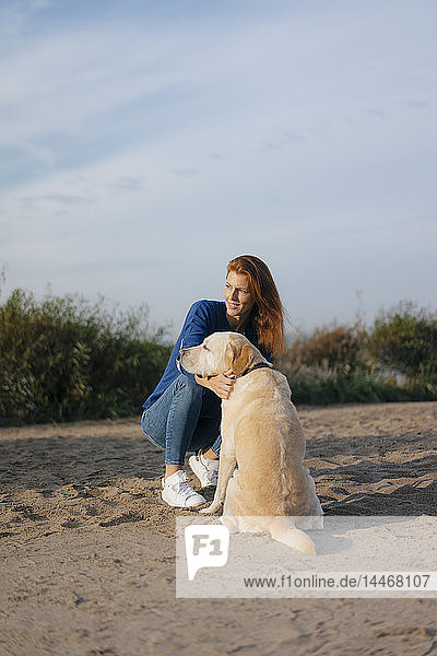 Deutschland,  Hamburg,  Frau mit Hund am Strand am Elbufer