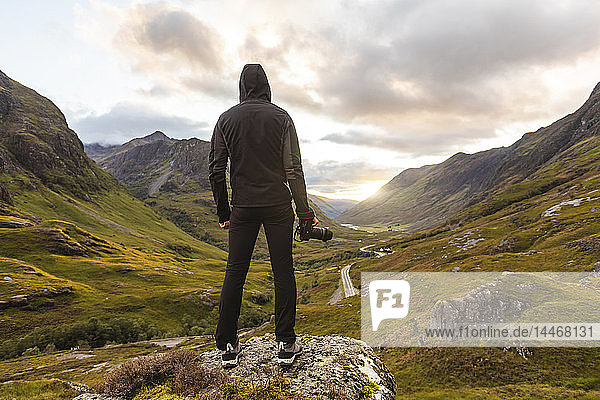 UK,  Scotland,  Man looking at view with the Three Sisters of Glencoe mountains on the left and the A82 road in the middle of the valley