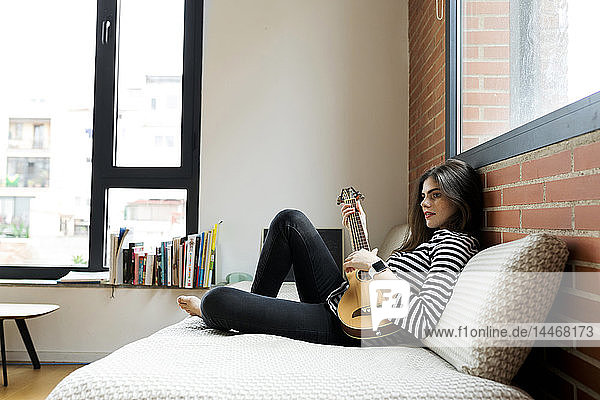 Junge Frau sitzt zu Hause auf dem Sofa und spielt Gitarre