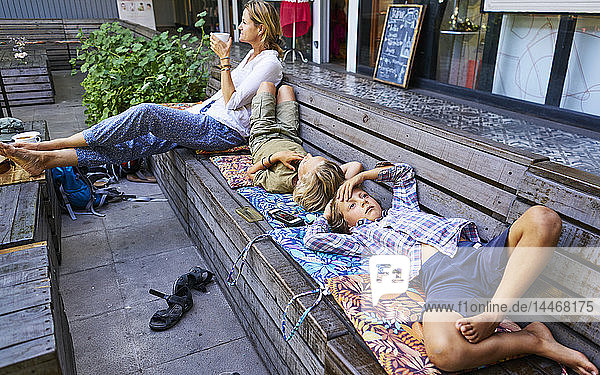 Mother and two sons relaxing on a bench