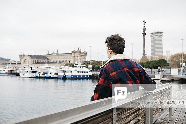Junger Mann in legerer Kleidung sitzt auf einer Bank im Hafen