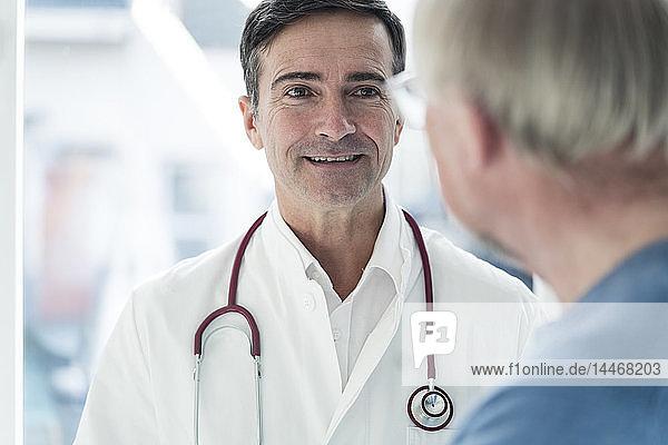 Porträt eines lächelnden Arztes  der den Patienten anschaut