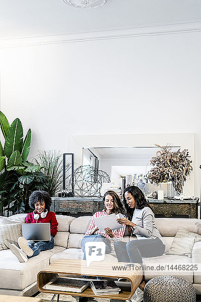 Three women with laptop and documents sitting on couch