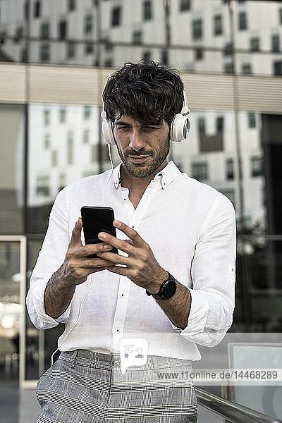 Junger Mann mit Kopfhörern und Handy in der Stadt
