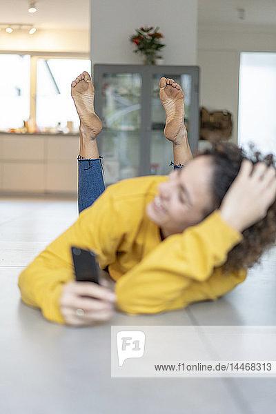 Glückliche Frau mit schmutzigen nackten Füßen  die zu Hause auf dem Boden liegt