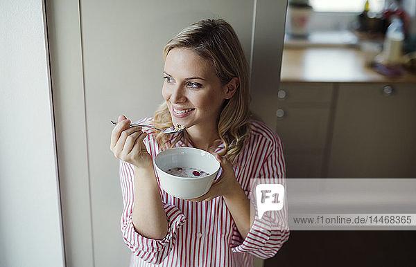 Lächelnde Frau frühstückt morgens zu Hause