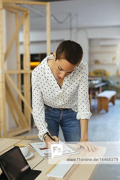 Frau arbeitet am Schreibtisch im Büro an einem Entwurf