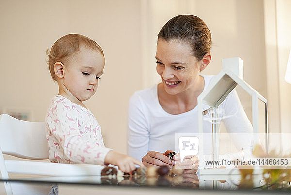 Happy mother and little daughter tinkering autumnal decorative house at home