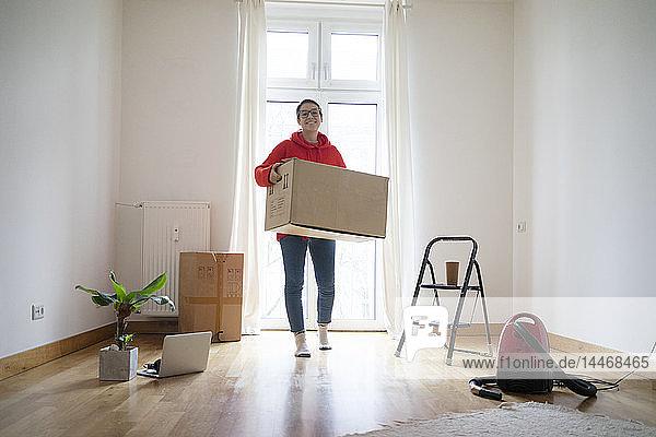 Junge Frau zieht in ihr neues Zuhause ein und trägt einen Pappkarton