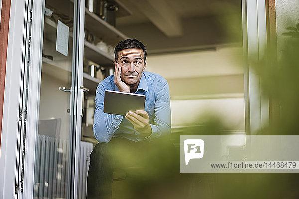 Geschäftsmann mit Tablett vor offener Fenstertür sitzend