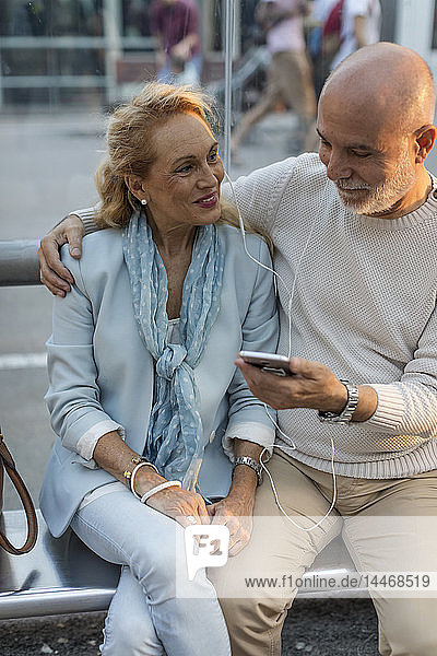 Spanien  Barcelona  ein älteres Ehepaar sitzt an einer Straßenbahnhaltestelle in der Stadt und teilt sich ein Smartphone mit Ohrstöpseln