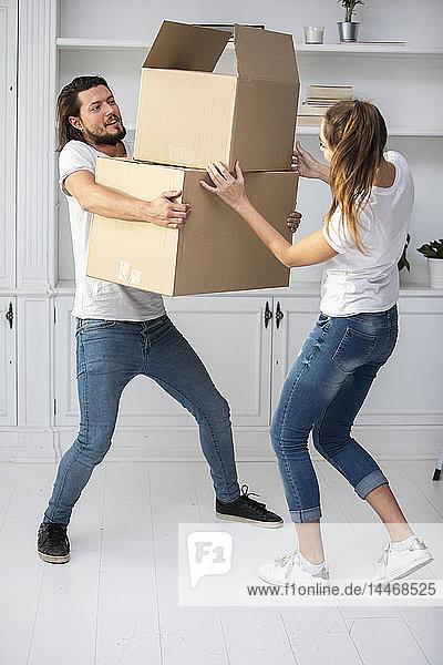 Paar mit Freundin trägt Pappkartons im neuen Zuhause